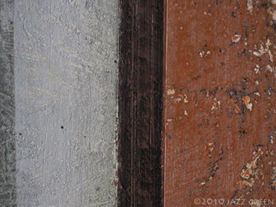 detail of abstract painting on wood - eroded weathered orange, brown, grey