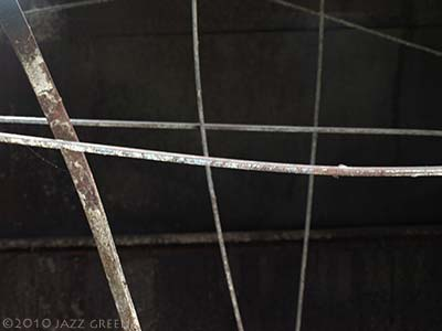 photograph of rusted iron bars intersecting dark space - like a drawing