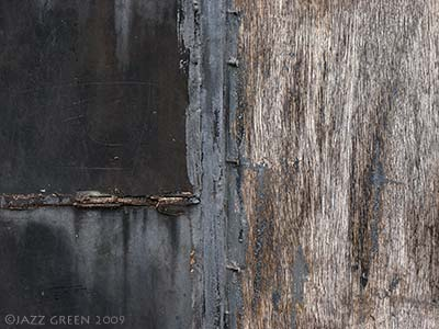 photograph - weathered wall facade, wood textures - brown black grey