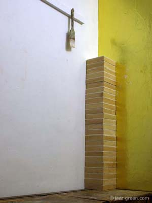 wood panels neatly stacked up - upright column - sculpture - artist studio